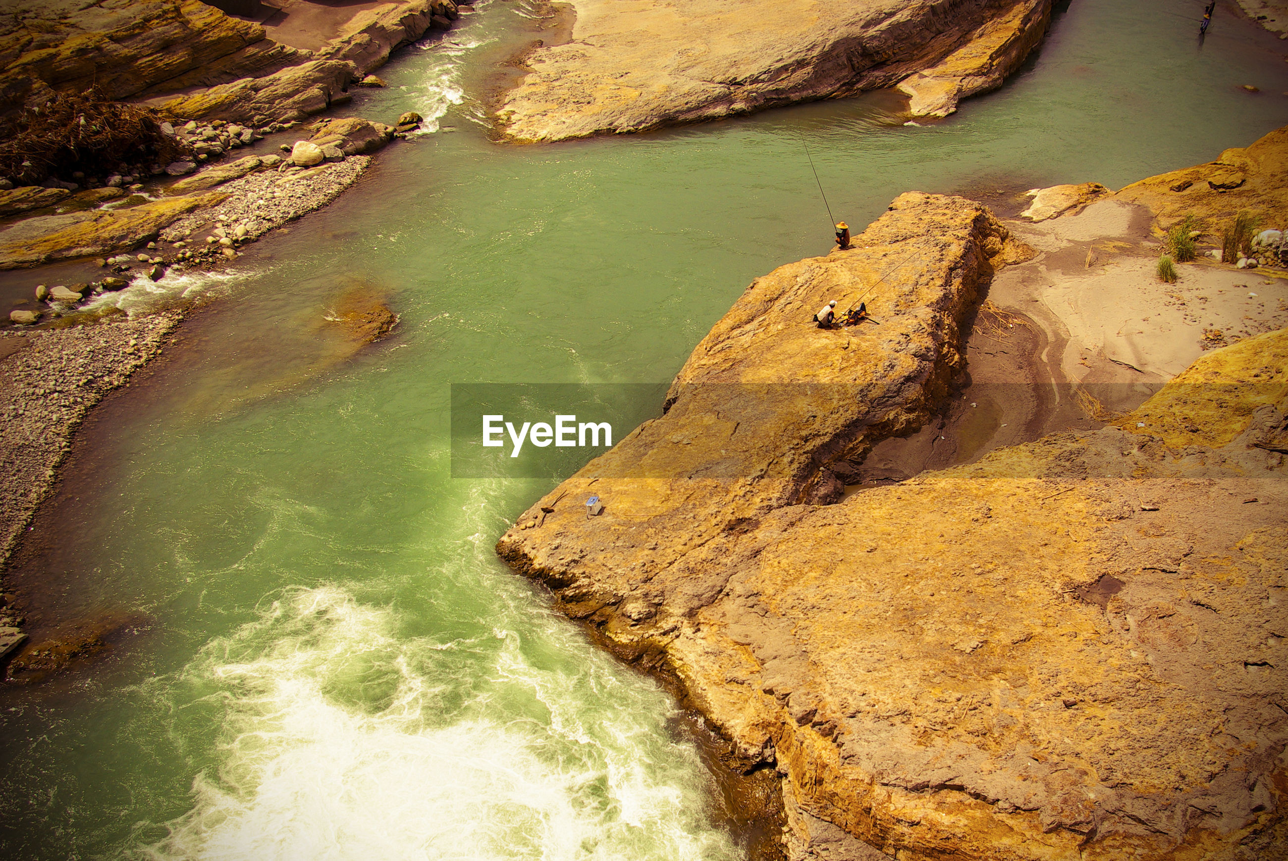 HIGH ANGLE VIEW OF ROCK FORMATIONS BY RIVER