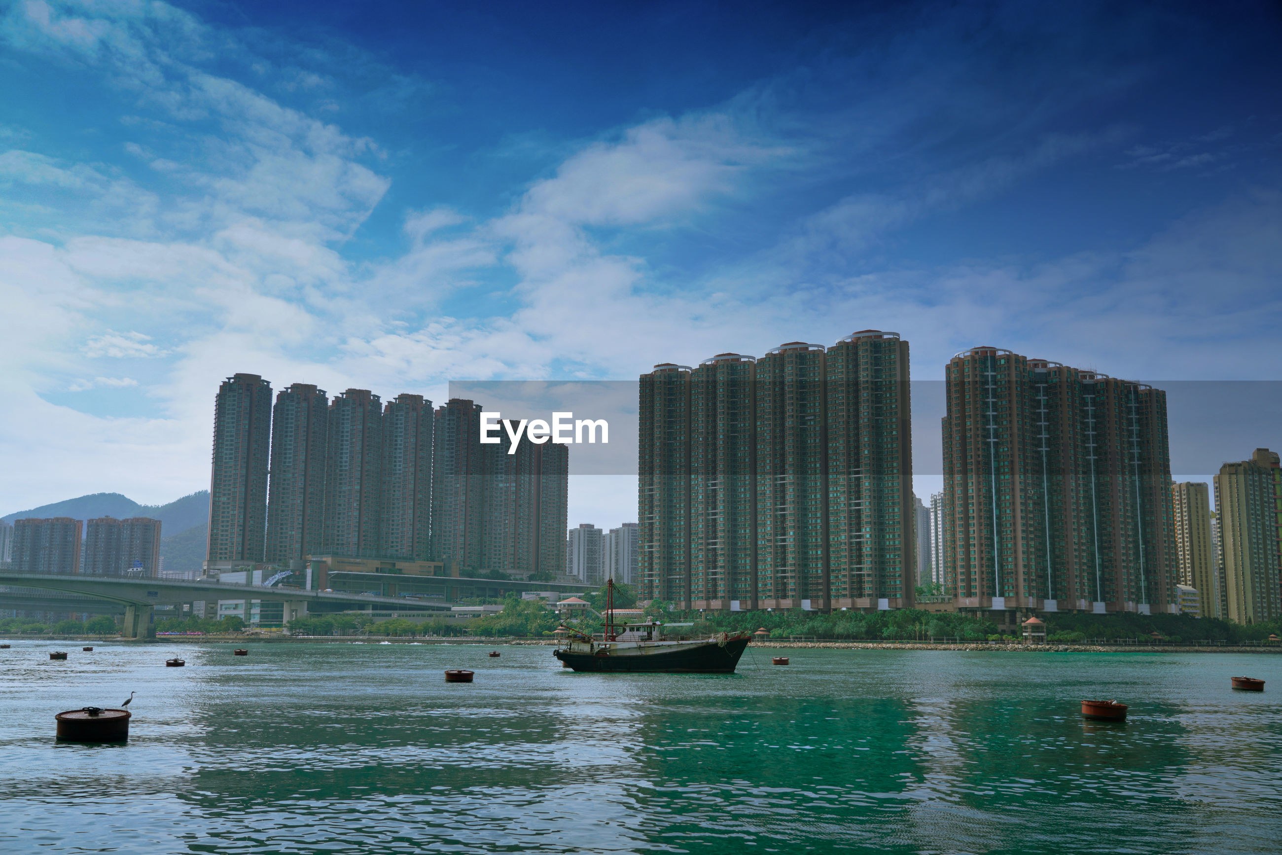 BOATS IN SEA BY BUILDINGS AGAINST SKY IN CITY