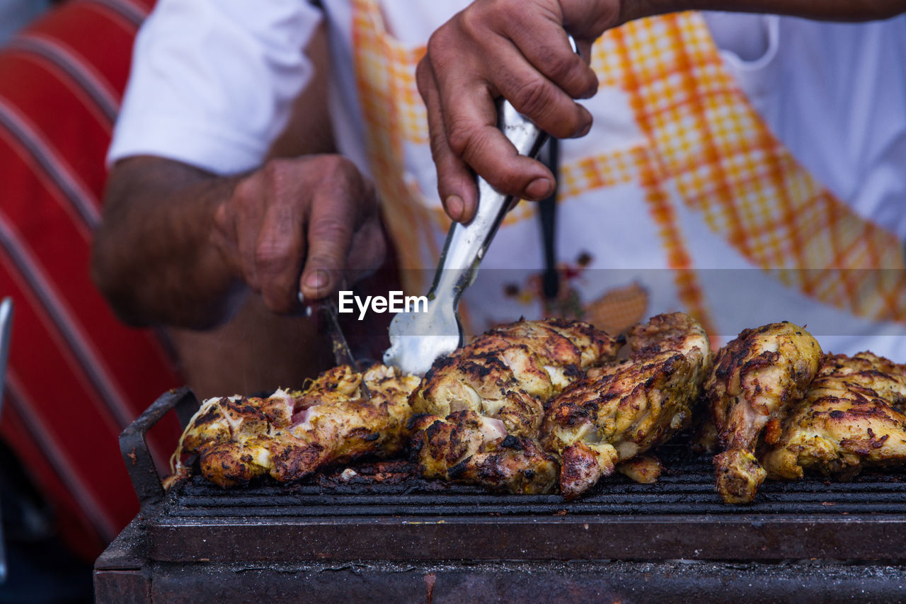 Cropped Image Of Man Grilling Chicken At Market Stall