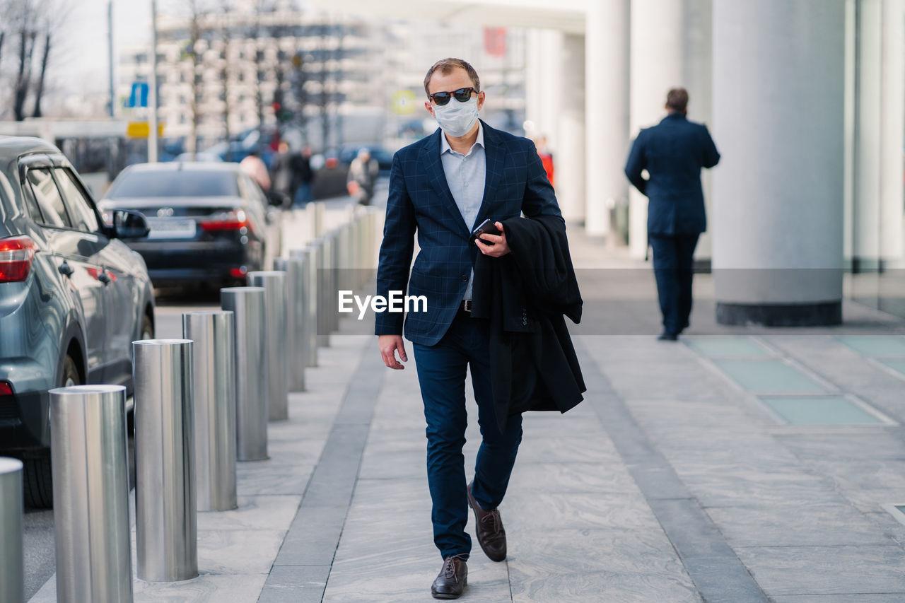 Businessman wearing mask walking in city
