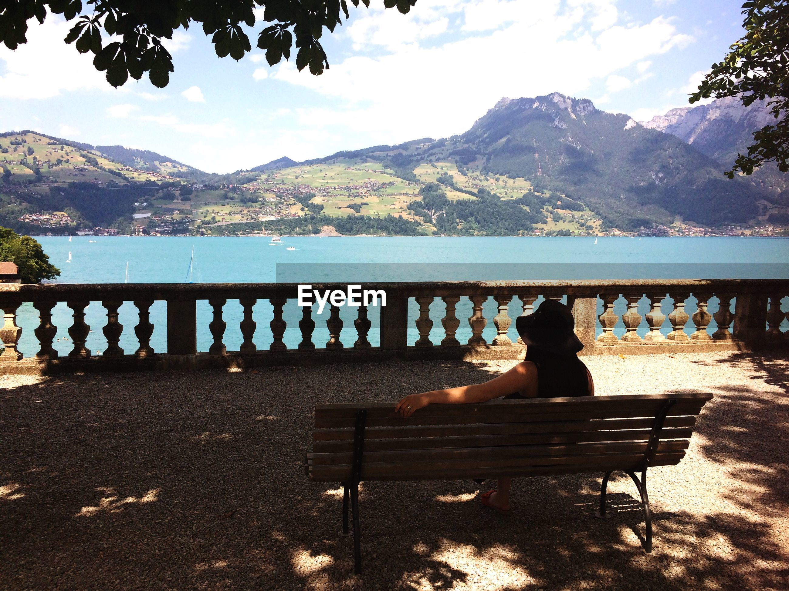 Rear view of woman sitting on bench while looking at sea and mountains