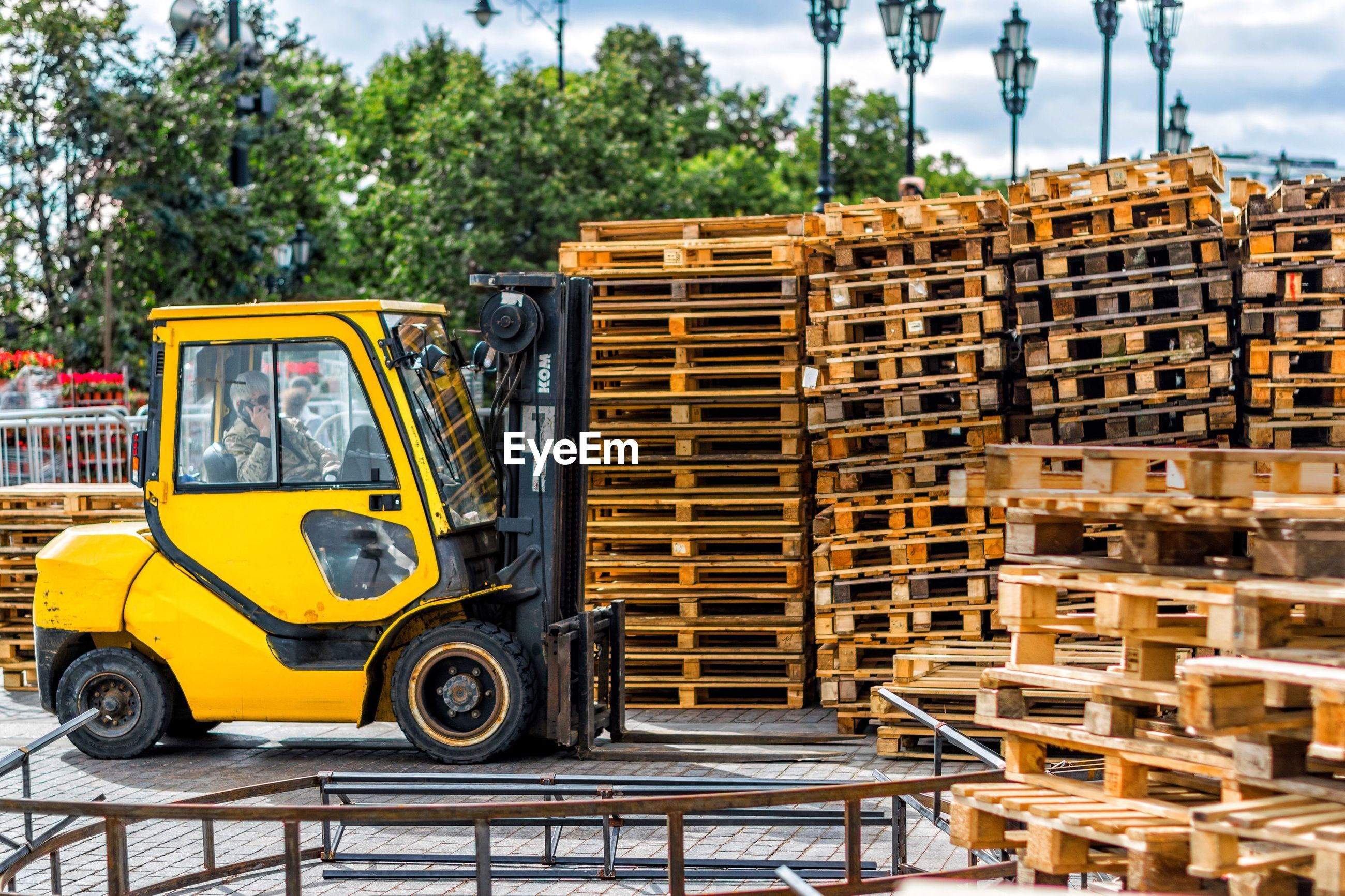 Forklift by wooden objects against trees