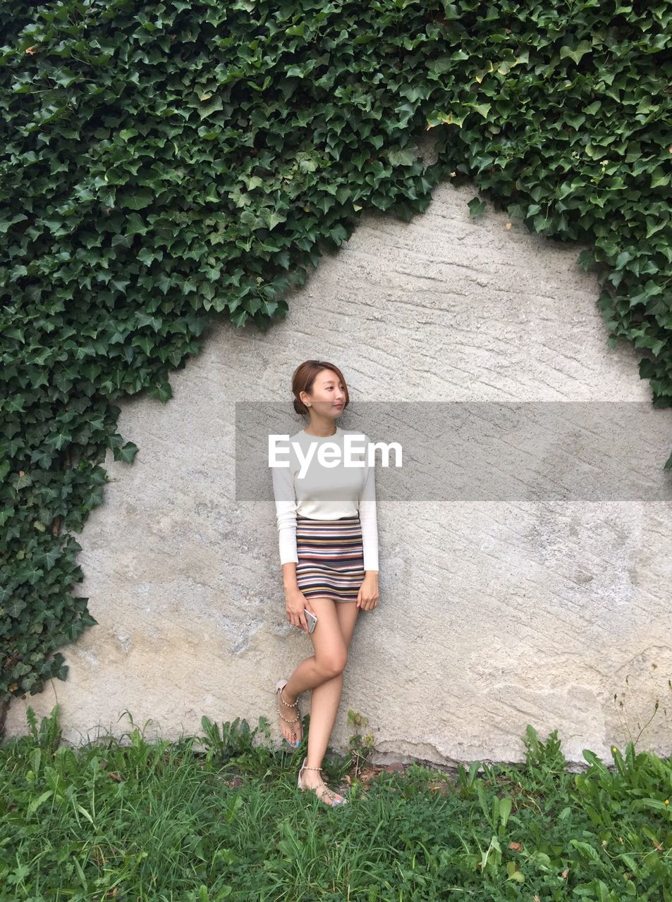 Young woman standing against wall with ivy