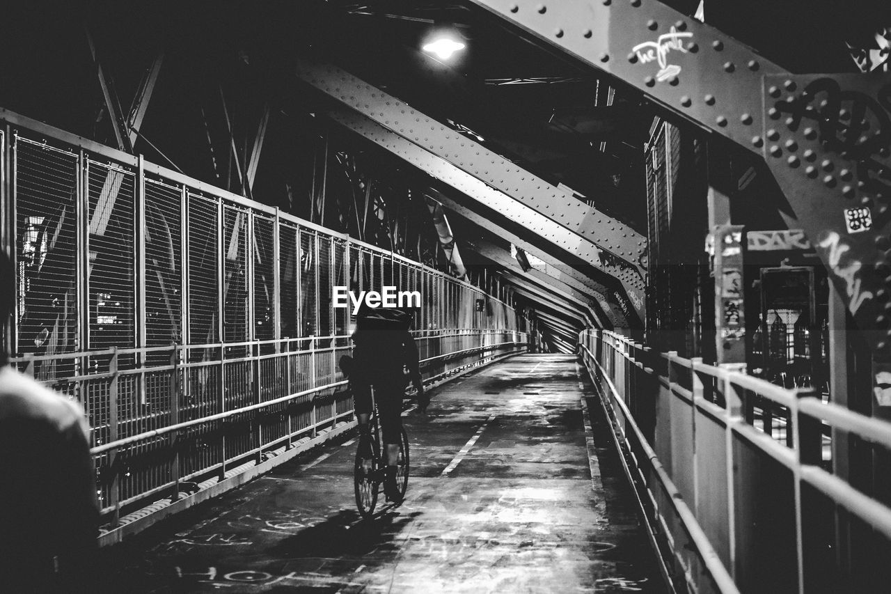 Person riding bicycle on bridge at night