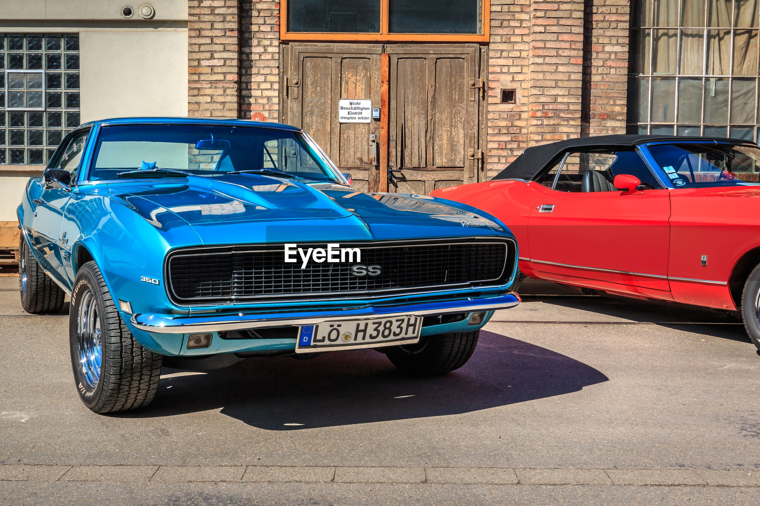 car, mode of transportation, land vehicle, motor vehicle, transportation, architecture, blue, built structure, building exterior, city, day, street, retro styled, vintage car, stationary, building, outdoors, no people, sunlight, luxury, garage
