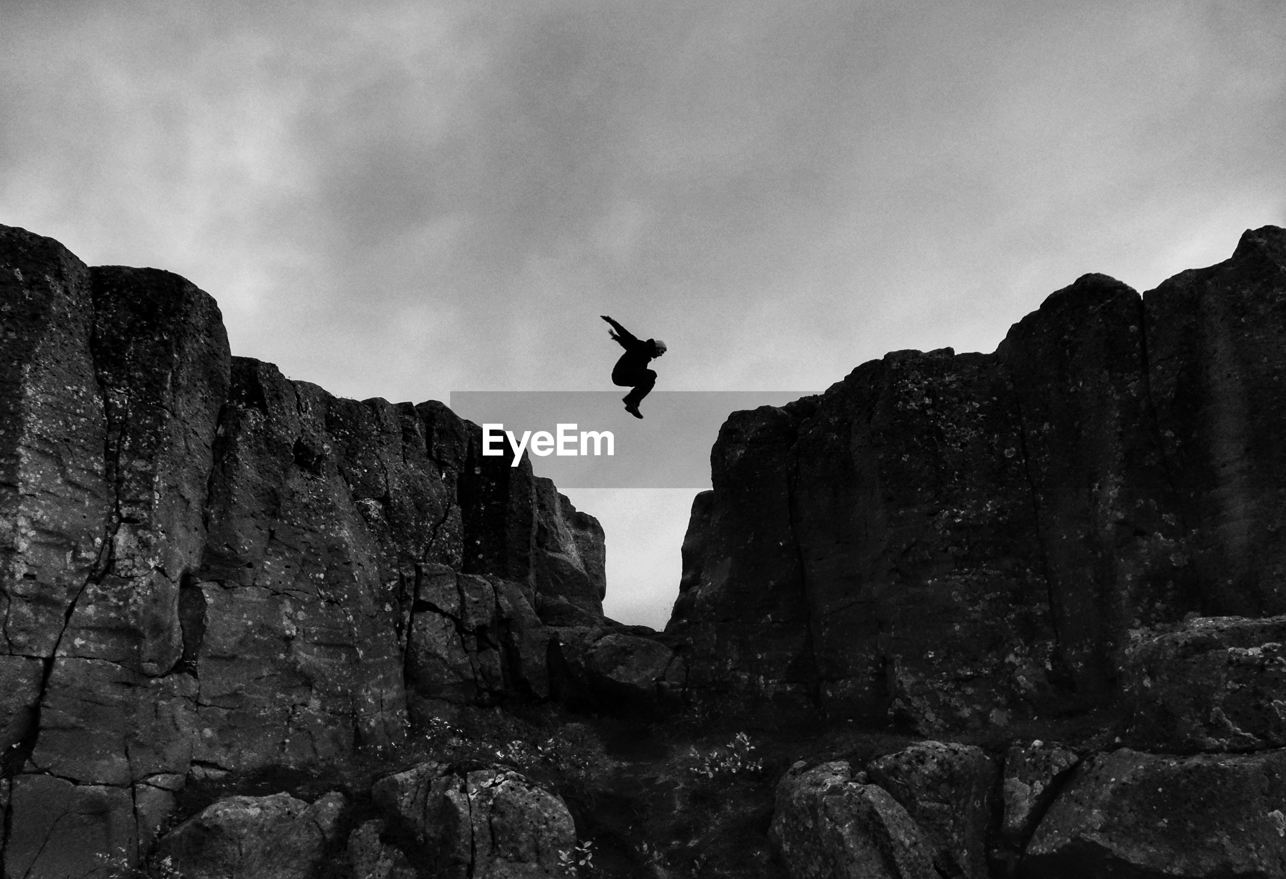 Low angle view of silhouette man jumping over rocks