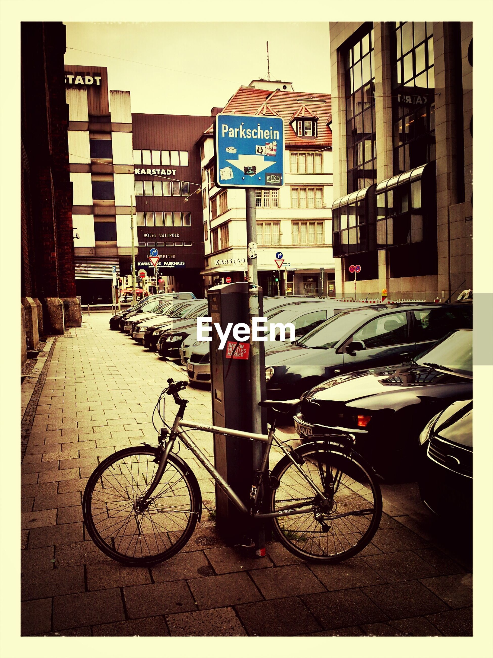 bicycle, transportation, mode of transport, land vehicle, building exterior, parked, architecture, stationary, built structure, parking, street, city, car, auto post production filter, transfer print, day, parking lot, building, outdoors, sidewalk