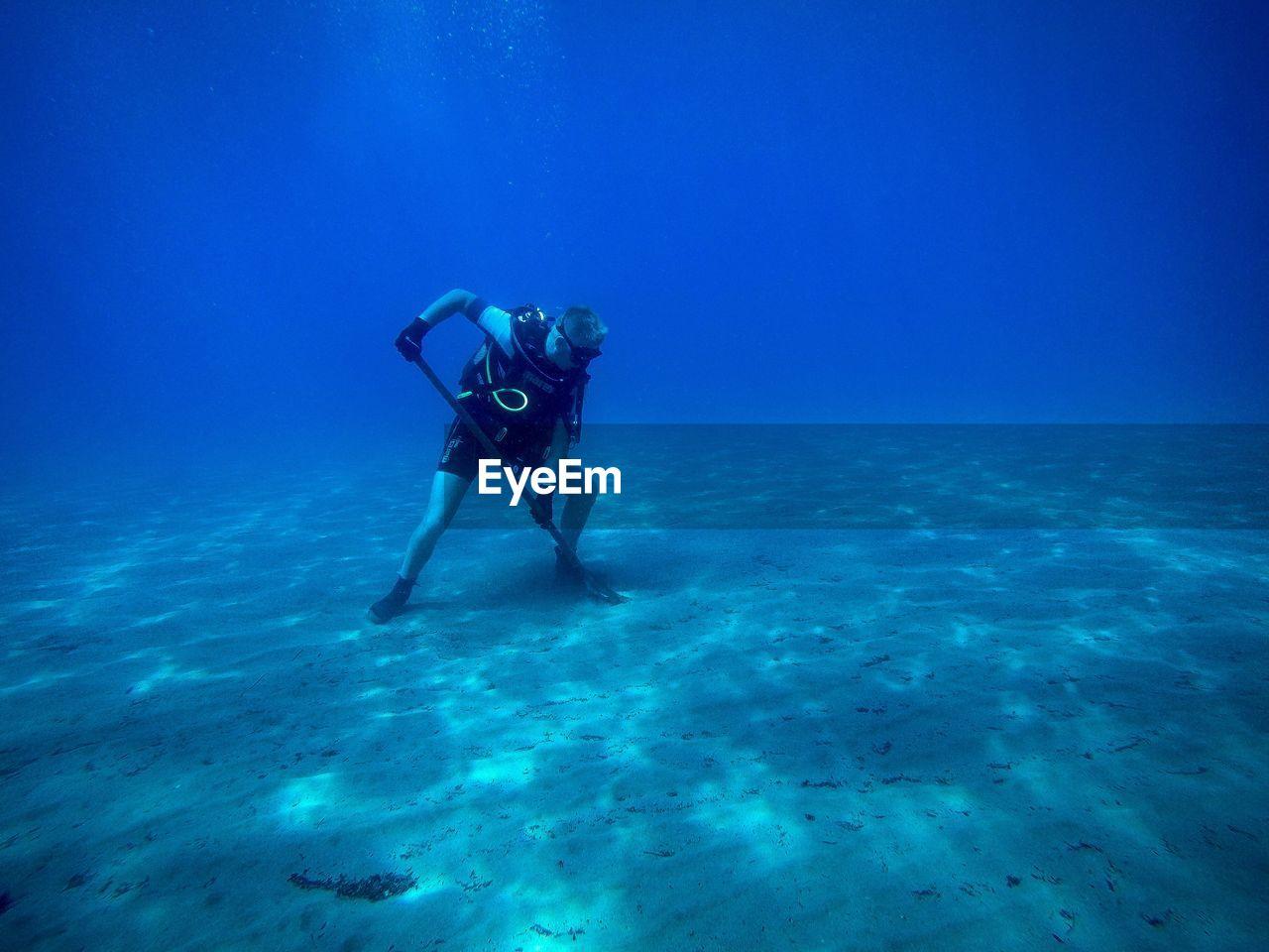 Scuba diver digging ocean floor