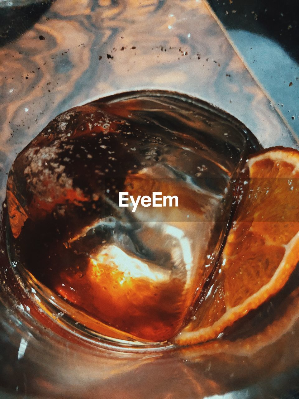 A glass of whiskey with an ice cube and an orange slice