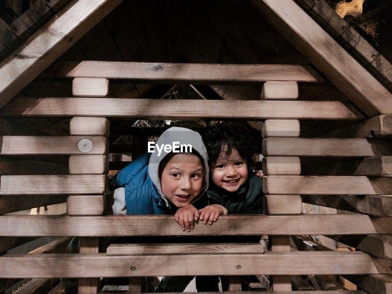 Siblings Peeking From Window Of Tree House