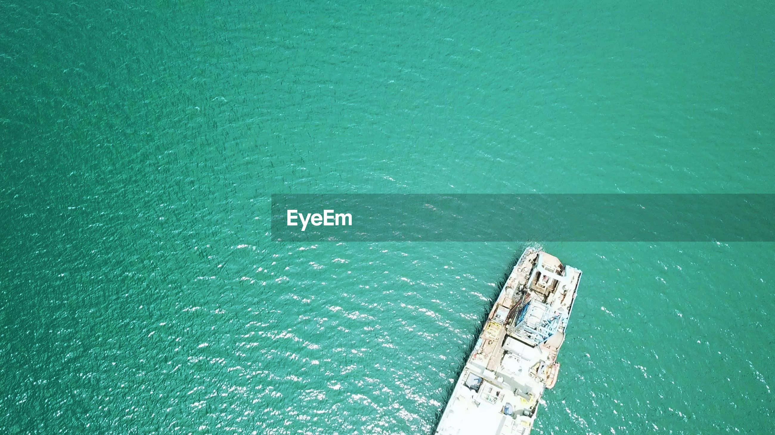 HIGH ANGLE VIEW OF SHIP IN SEA AGAINST GREEN BLUE SKY