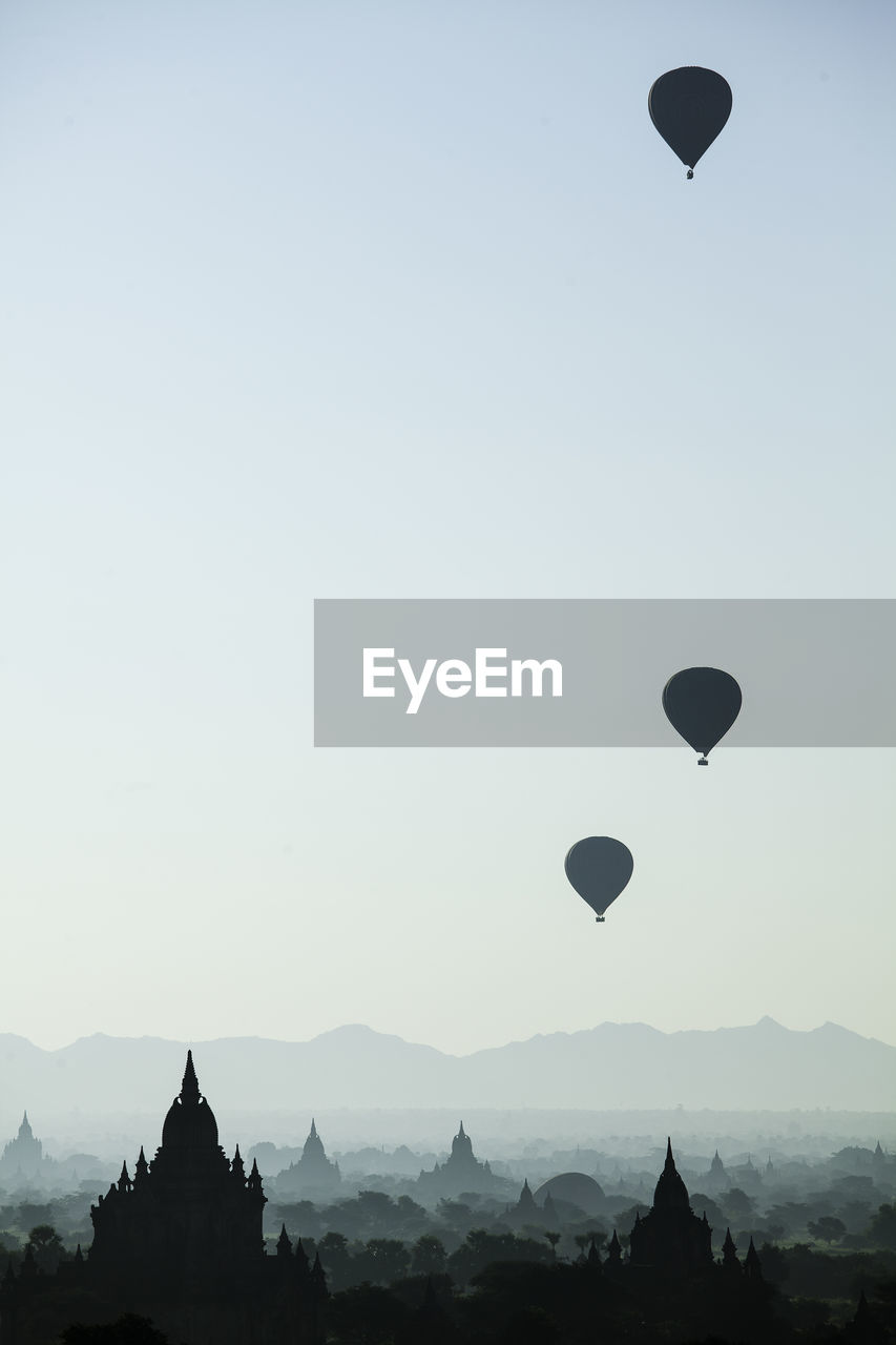 sky, balloon, hot air balloon, air vehicle, mid-air, clear sky, flying, nature, scenics - nature, transportation, beauty in nature, adventure, silhouette, architecture, building exterior, travel, copy space, no people, travel destinations, built structure, outdoors