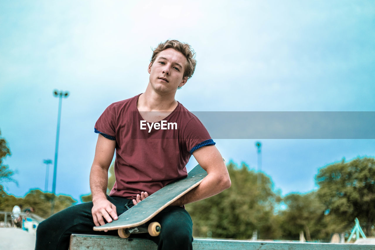 Portrait Of Young Man With Skateboard Sitting Against Sky