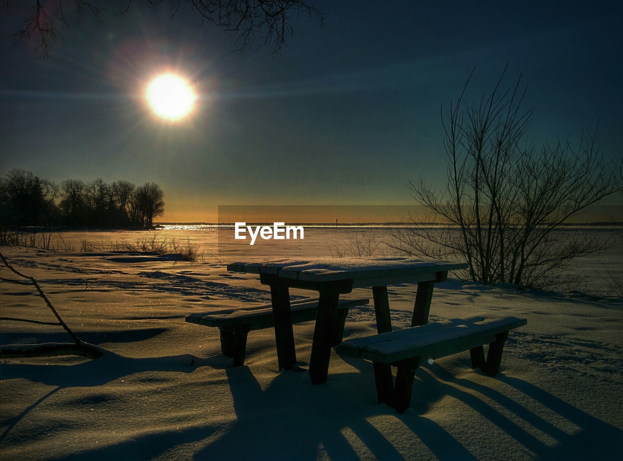 Snow covered bench on field against sky during sunset