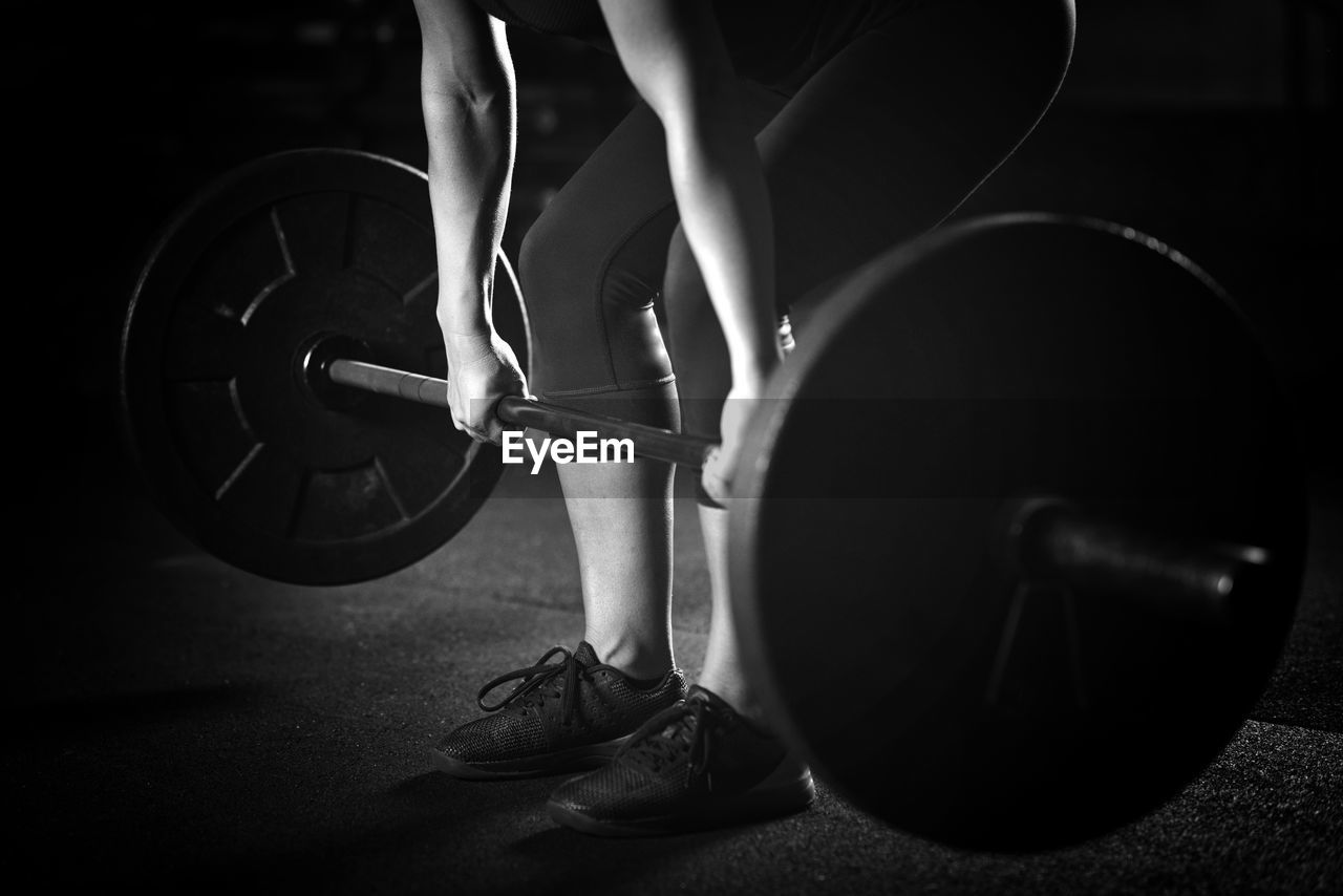 Low Section Of Woman Lifting Barbell