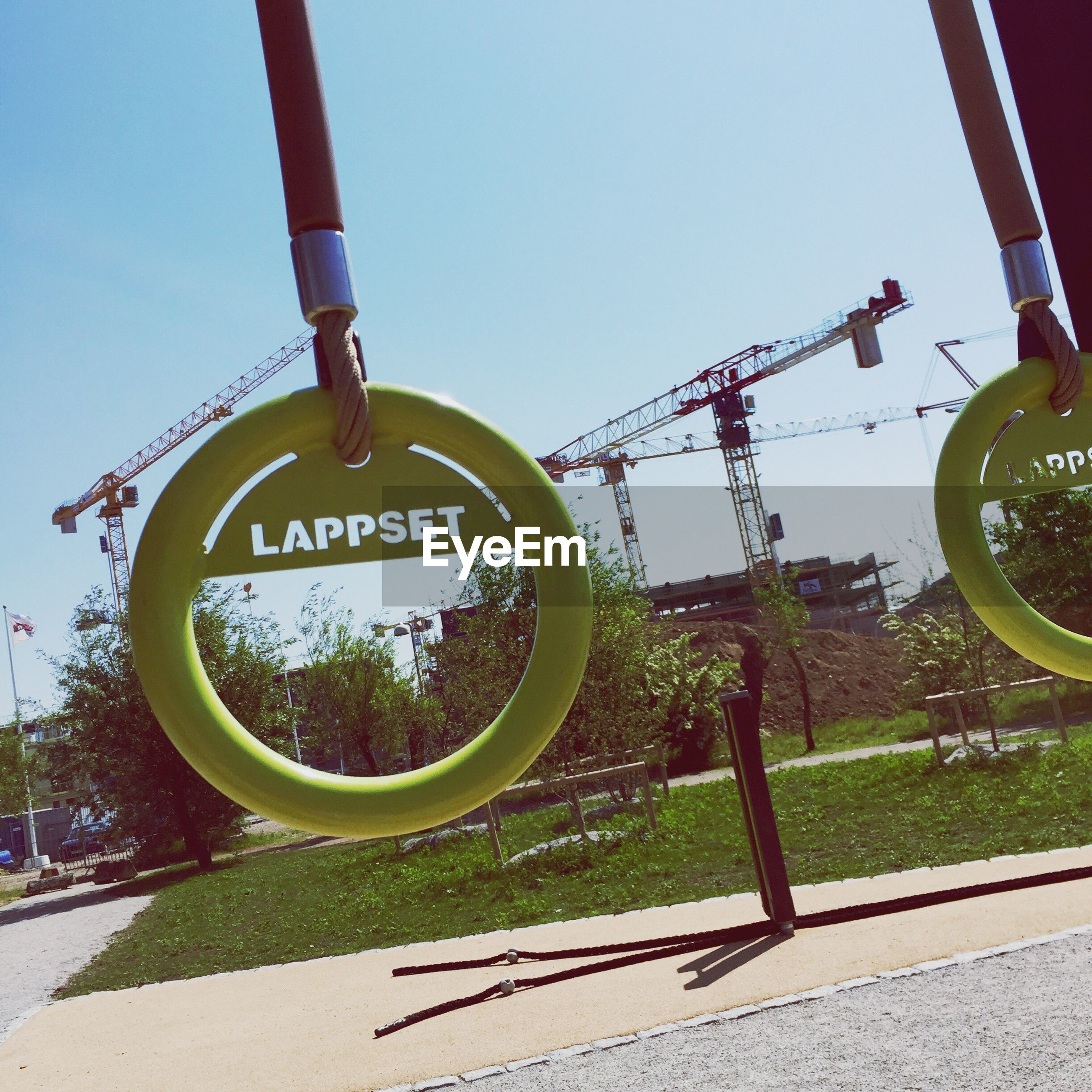 Close-up of text on gymnastic rings at park against crane
