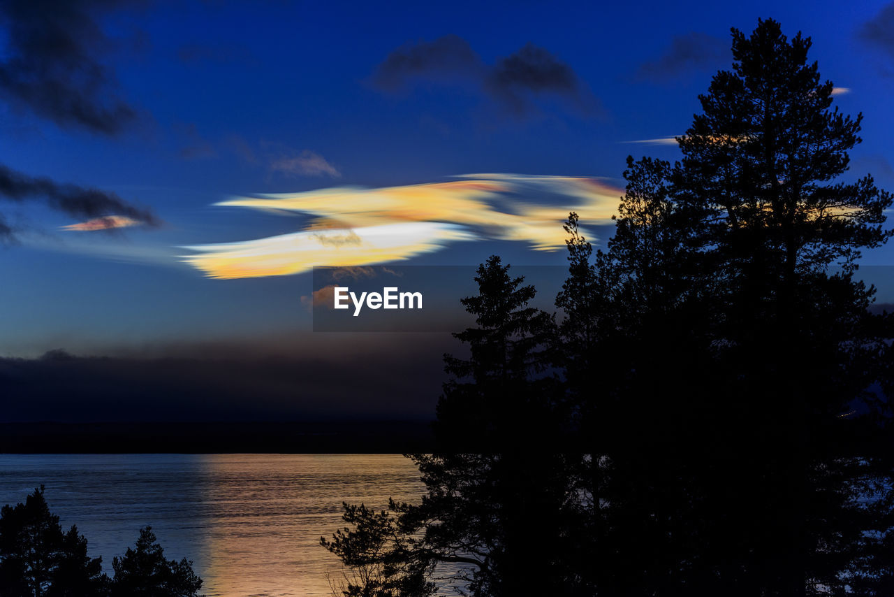Scenic view of lake against  noctilucent clouds sky at sunset