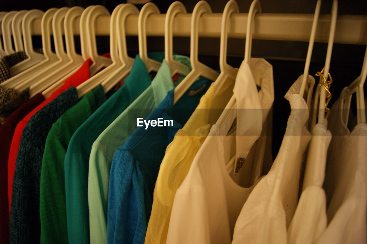 hanging, clothing, coathanger, variation, in a row, retail, choice, multi colored, store, clothing store, fashion, closet, rack, no people, large group of objects, indoors, consumerism, close-up, day