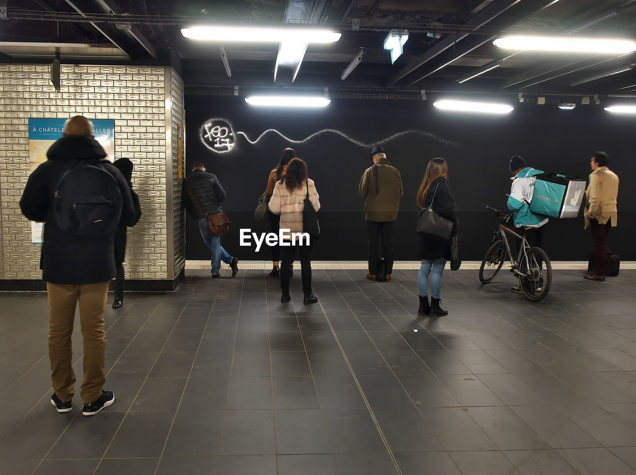 REAR VIEW OF PEOPLE WALKING IN ILLUMINATED UNDERGROUND