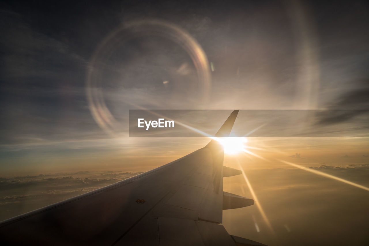 sky, cloud - sky, sunset, flying, air vehicle, mid-air, transportation, airplane, nature, sun, no people, mode of transportation, beauty in nature, scenics - nature, lens flare, sunlight, motion, outdoors, travel, aircraft wing, eclipse