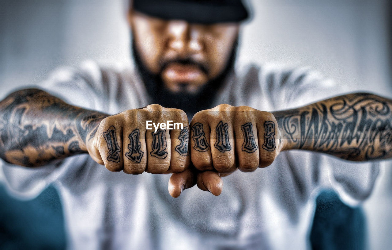 one person, front view, focus on foreground, real people, human hand, men, indoors, portrait, hand, lifestyles, looking at camera, communication, human body part, text, showing, young adult, close-up, young men, western script, aggression, finger, human arm