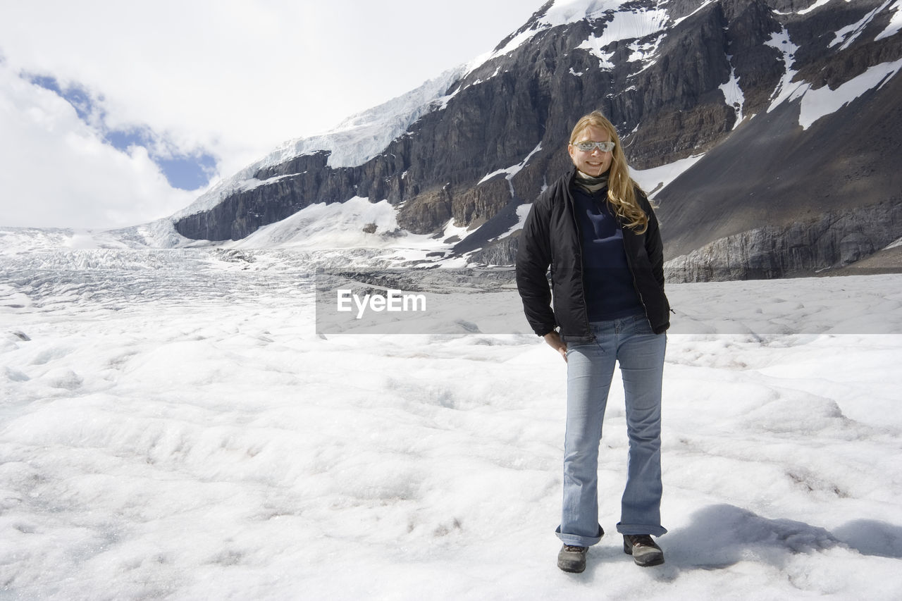Young Woman Standing Against Snowcapped Mountain