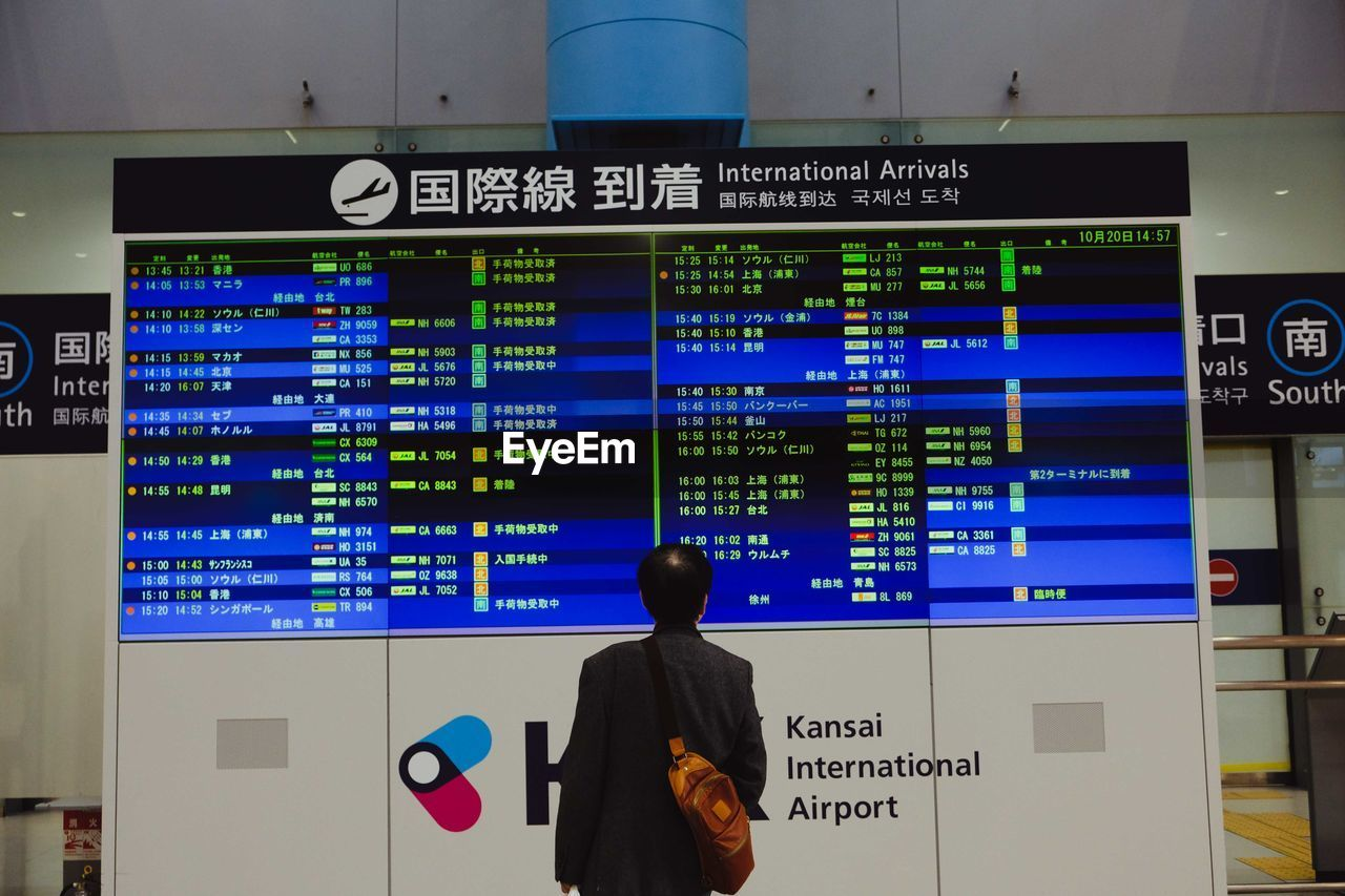 communication, one person, real people, technology, rear view, text, western script, men, airport, arrival departure board, public transportation, standing, information, transportation, indoors, script, screen, sign, illuminated, waiting