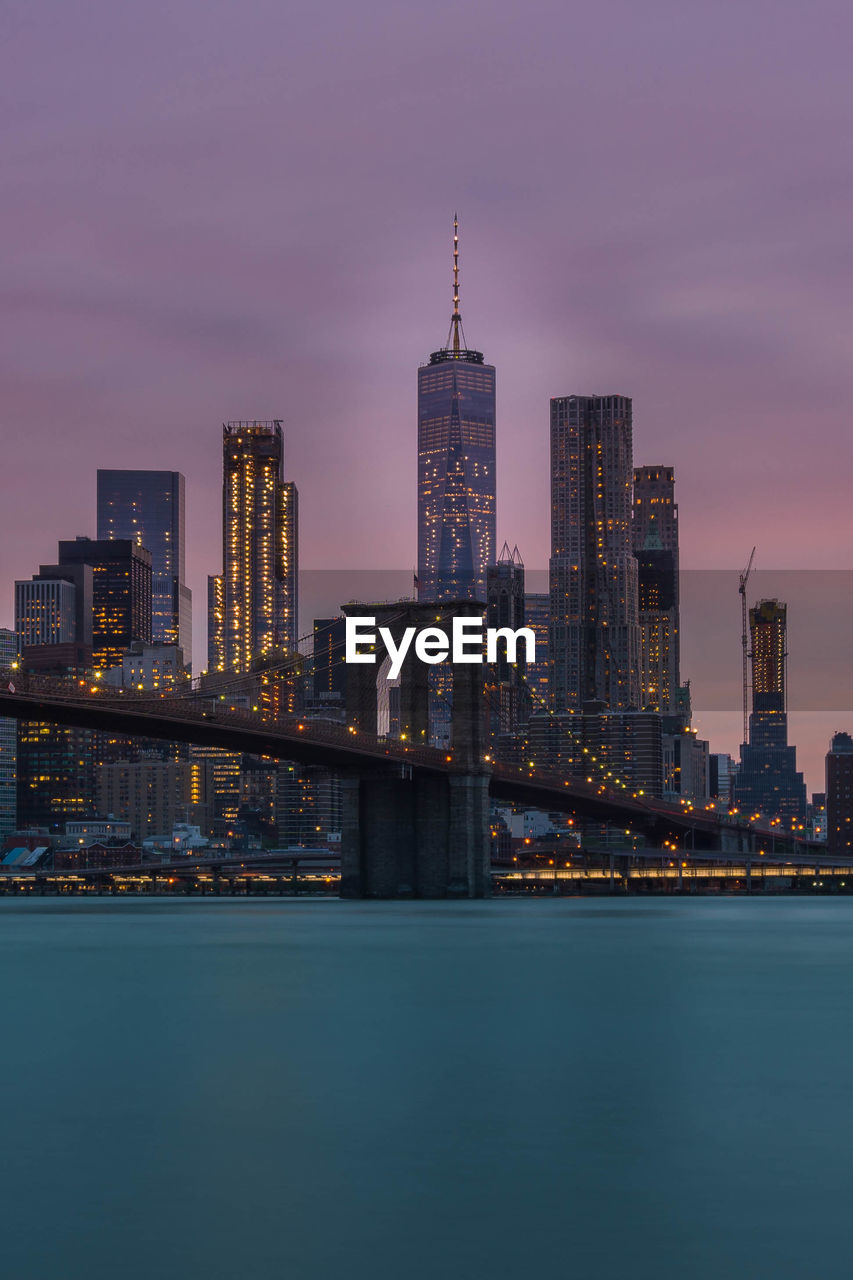 Low Angle View Of Illuminated Brooklyn Bridge Over River In City