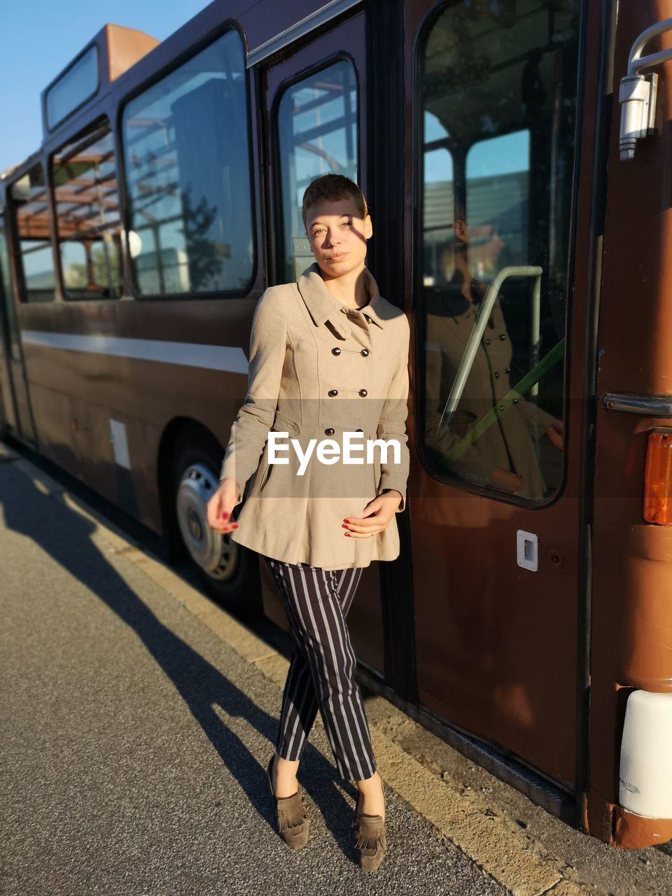 Portrait of woman walking by bus in city