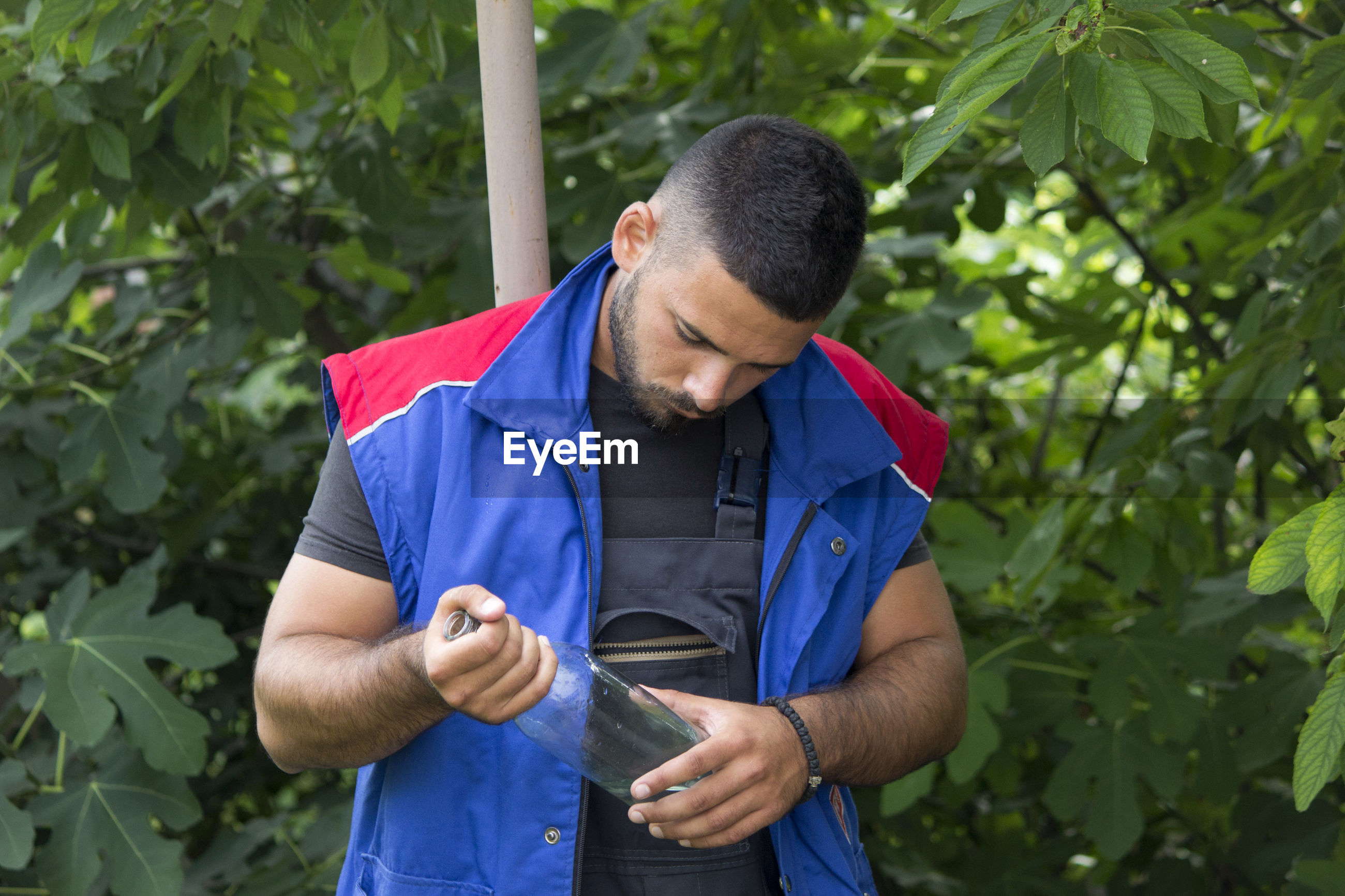YOUNG MAN LOOKING AWAY AGAINST PLANTS