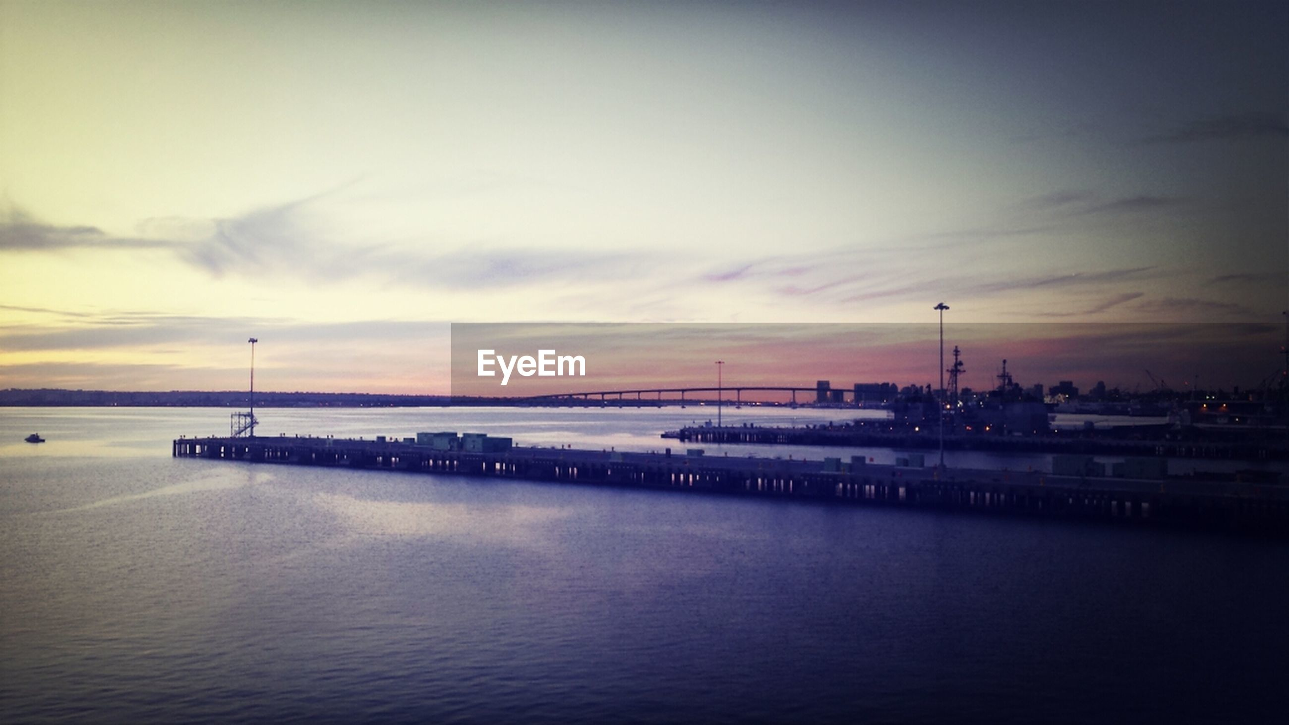 water, sea, sunset, sky, silhouette, waterfront, built structure, architecture, scenics, dusk, tranquility, tranquil scene, beauty in nature, building exterior, nature, cloud - sky, pier, illuminated, idyllic, reflection