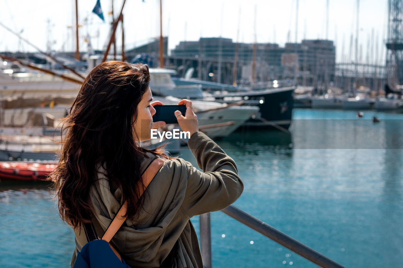 Rear view of woman photographing from mobile phone at harbor in city