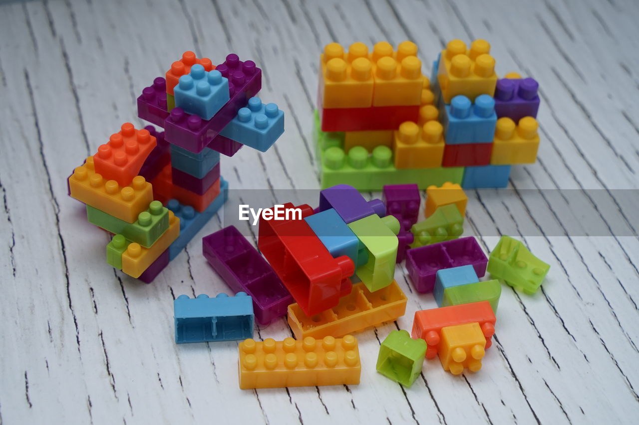 multi colored, toy, variation, still life, no people, high angle view, large group of objects, choice, indoors, close-up, table, toy block, plastic, yellow, leisure activity, design, focus on foreground, wood - material, block