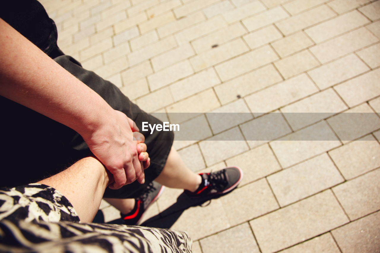 High angle view of homosexual couple holding hands while walking on footpath