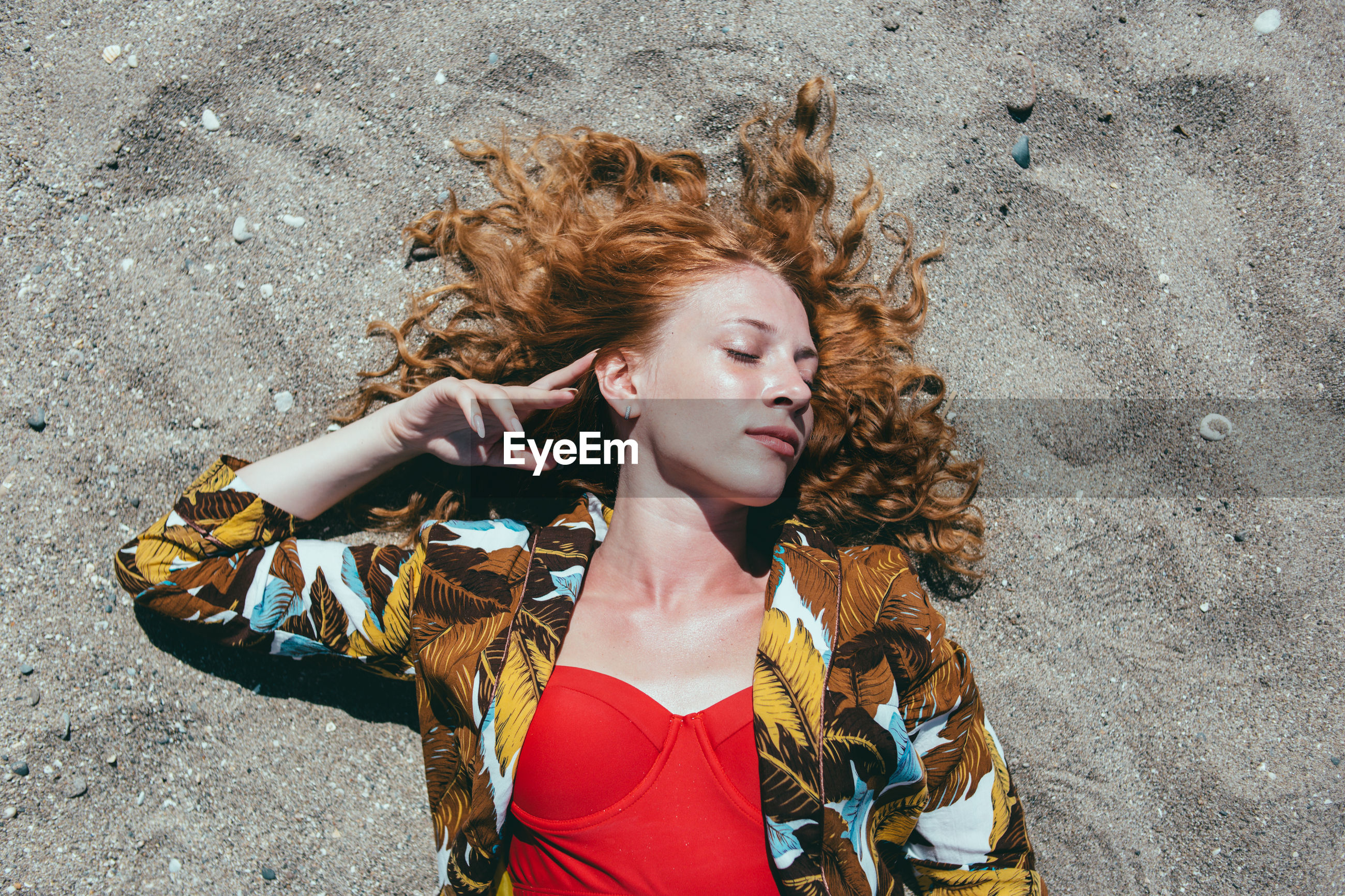 High angle view of young woman with eyes closed lying on sand