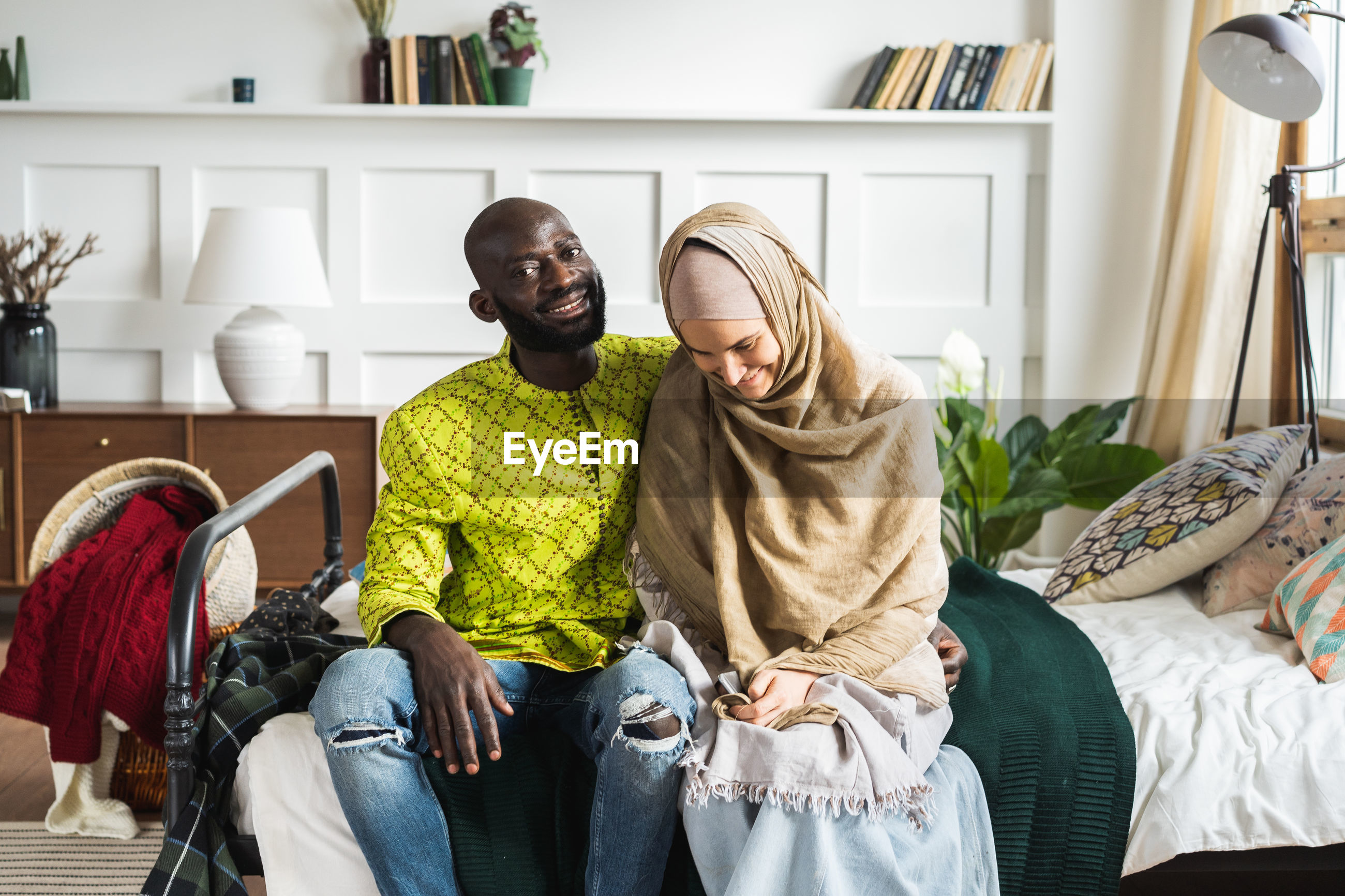 Smiling couple sitting on bed at home