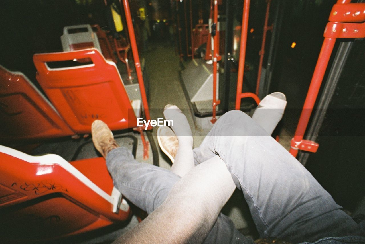 Two people sit with legs intertwined on a bus