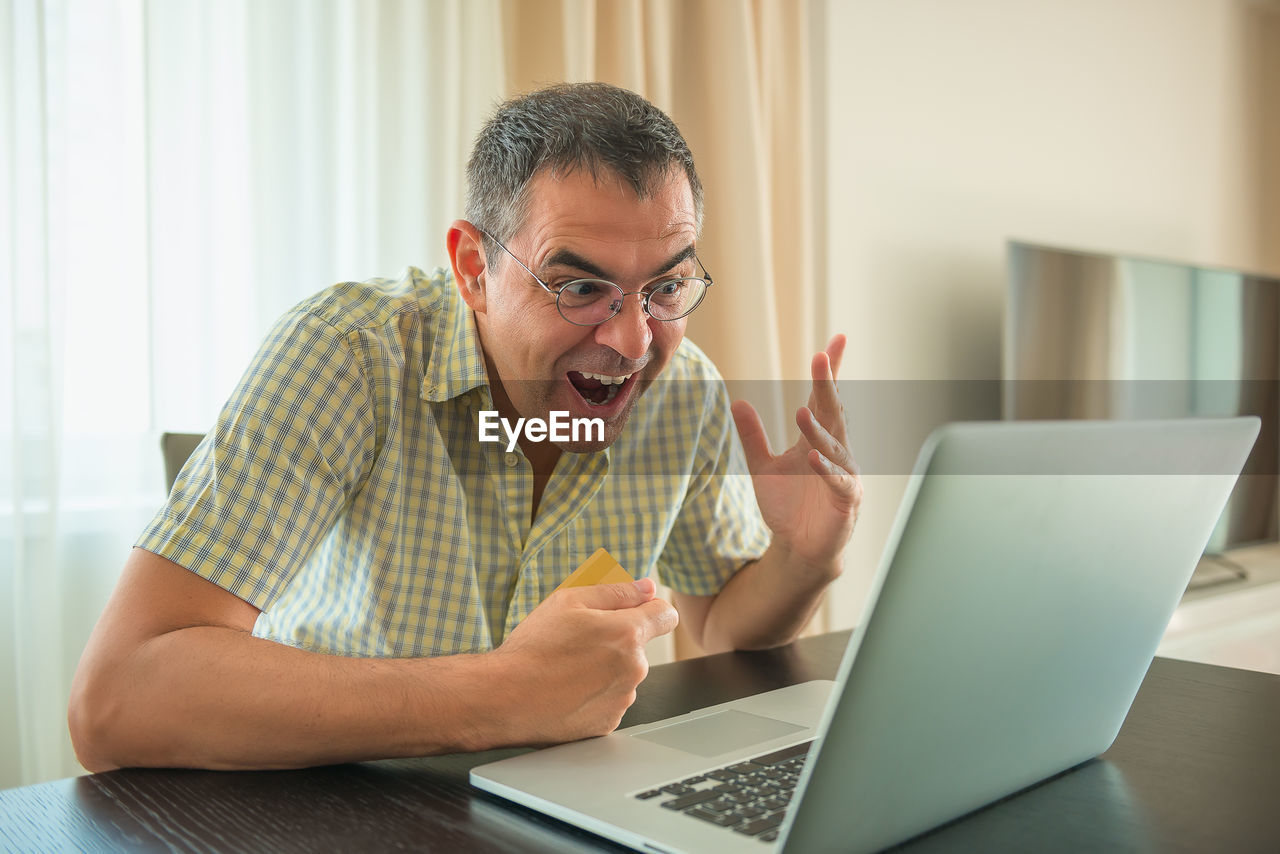 Mature man with mouth open using laptop on table while sitting at home