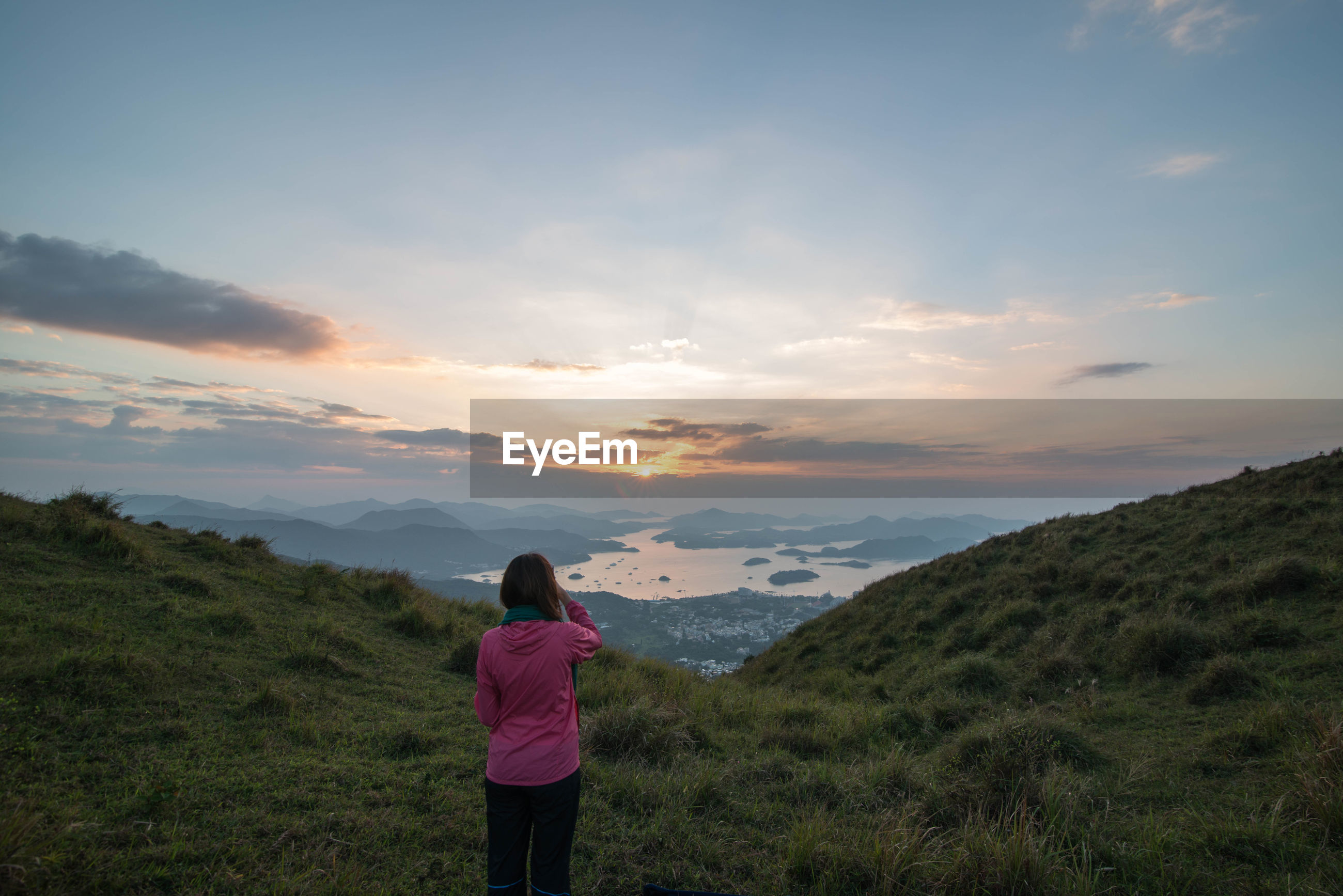 Rear view of woman standing on mountain against sky during sunrise