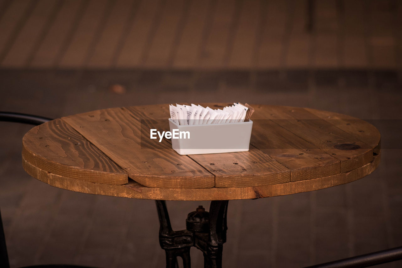 table, indoors, still life, focus on foreground, food and drink, wood - material, no people, food, high angle view, close-up, sweet food, seat, freshness, dessert, cake, selective focus, container, absence, ready-to-eat, event, temptation
