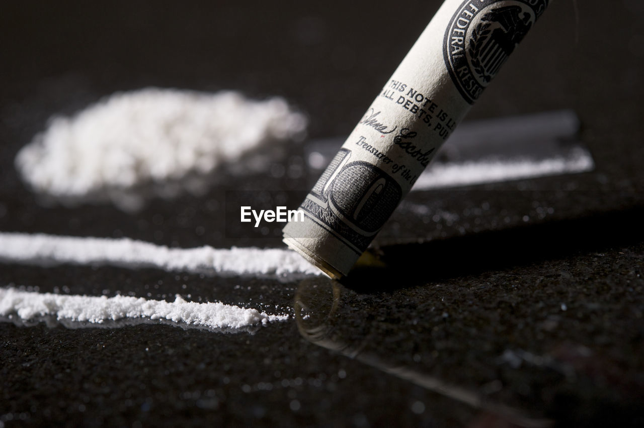Close Up Of Cocaine With Rolled Up American Currency On Table