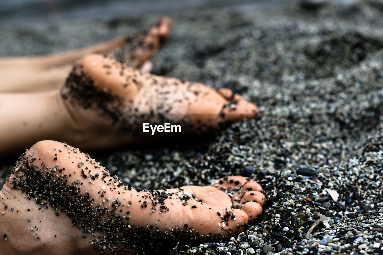 Close-up of barefoot on pebble beach
