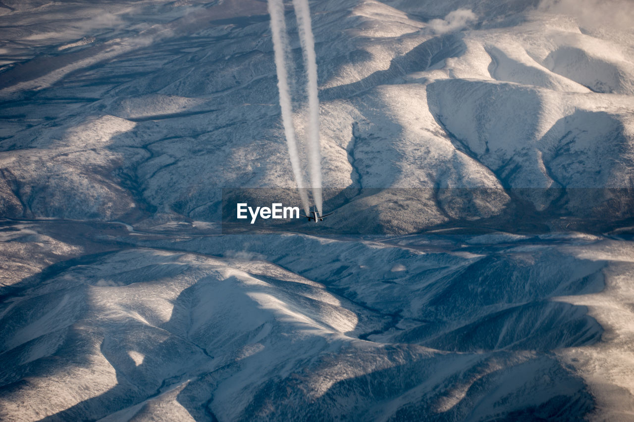 High angle view of snowcapped mountains with airliner