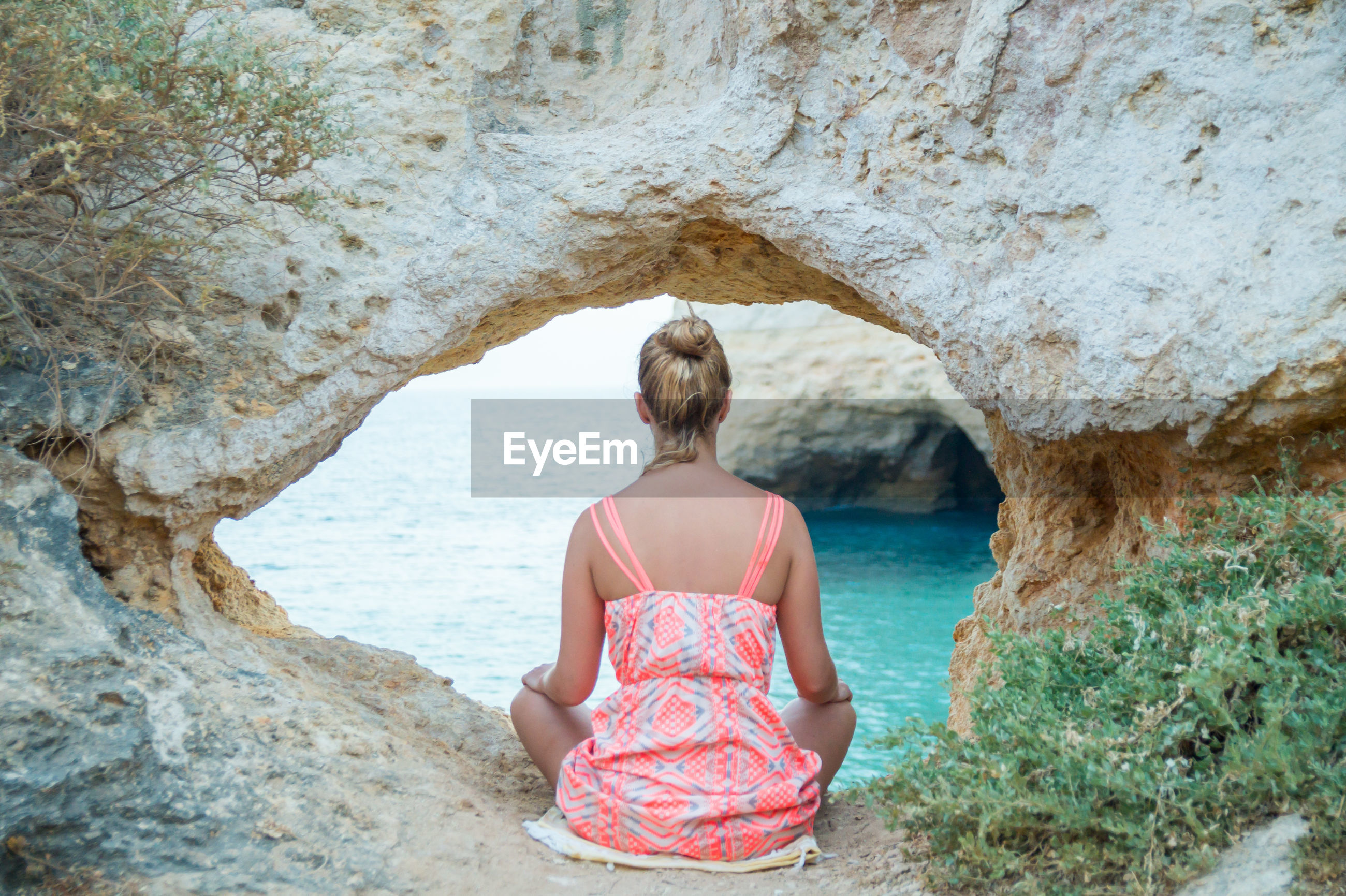 Rear view of woman looking at sea while sitting by rock