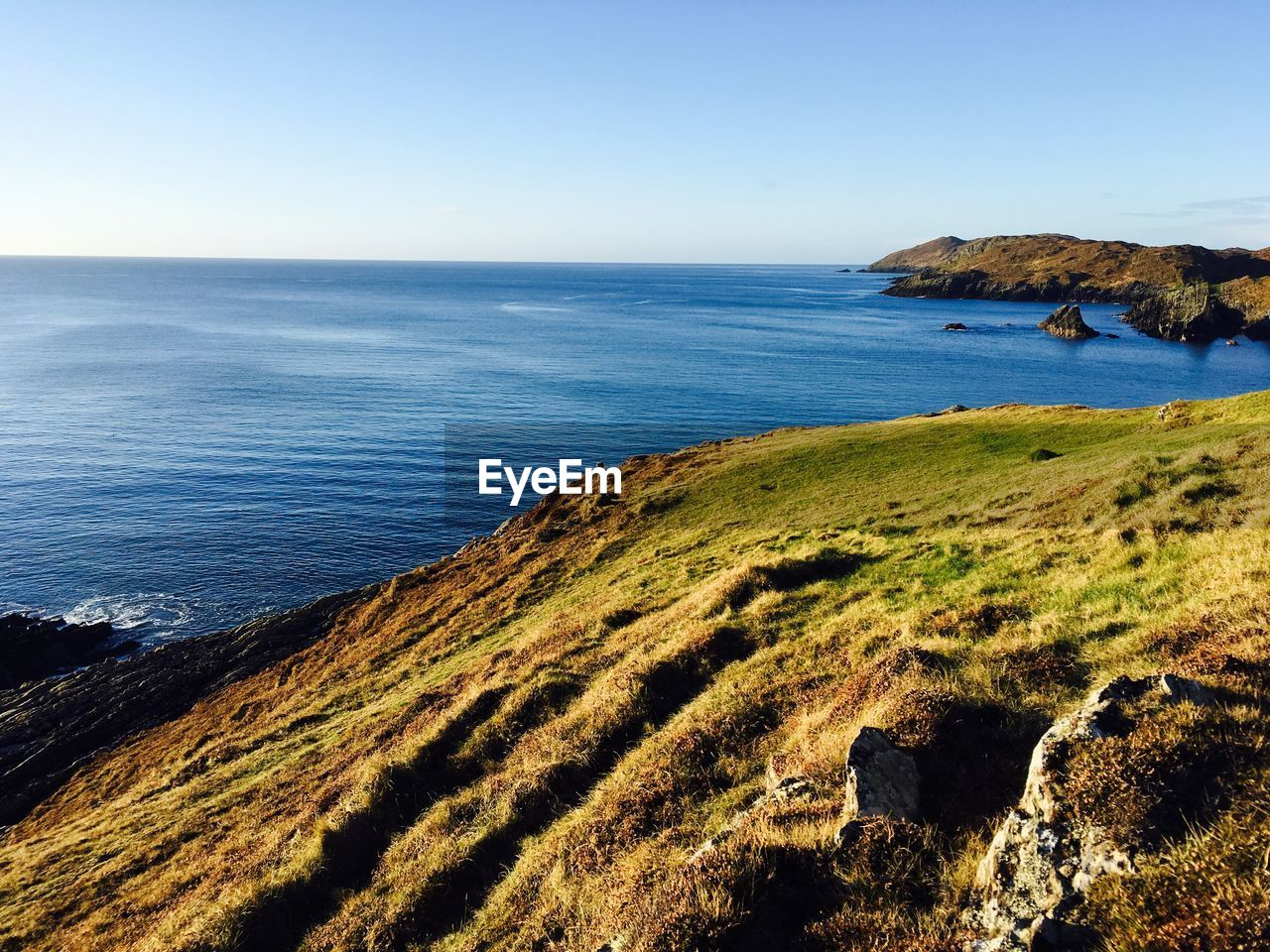 sea, nature, scenics, horizon over water, beauty in nature, tranquil scene, tranquility, water, clear sky, day, sunlight, cliff, grass, no people, outdoors, blue, sky