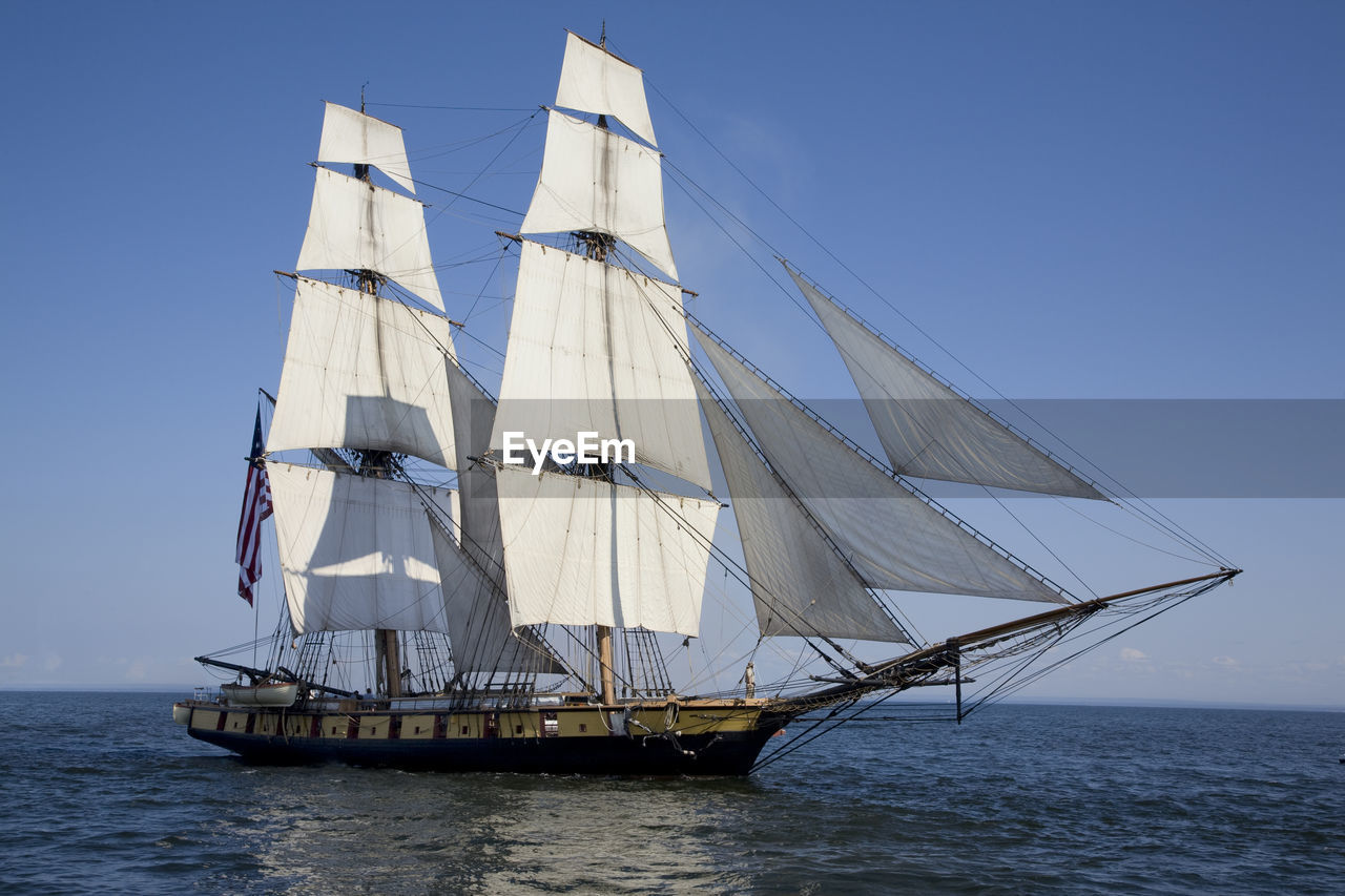 Tall ship sailing in lake superior against sky