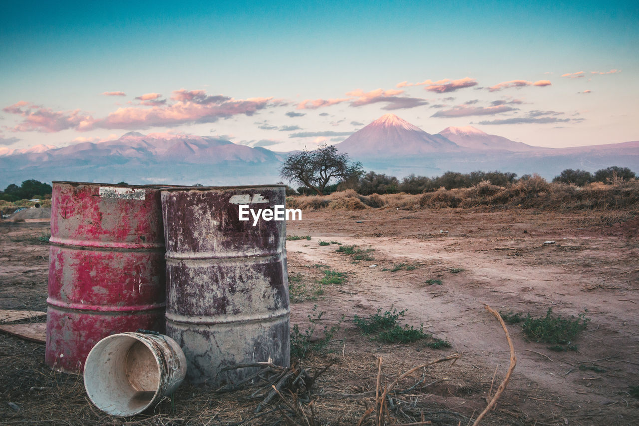 sky, cloud - sky, land, field, nature, no people, landscape, environment, metal, barrel, cylinder, day, mountain, abandoned, drum - container, scenics - nature, outdoors, container, non-urban scene, plant