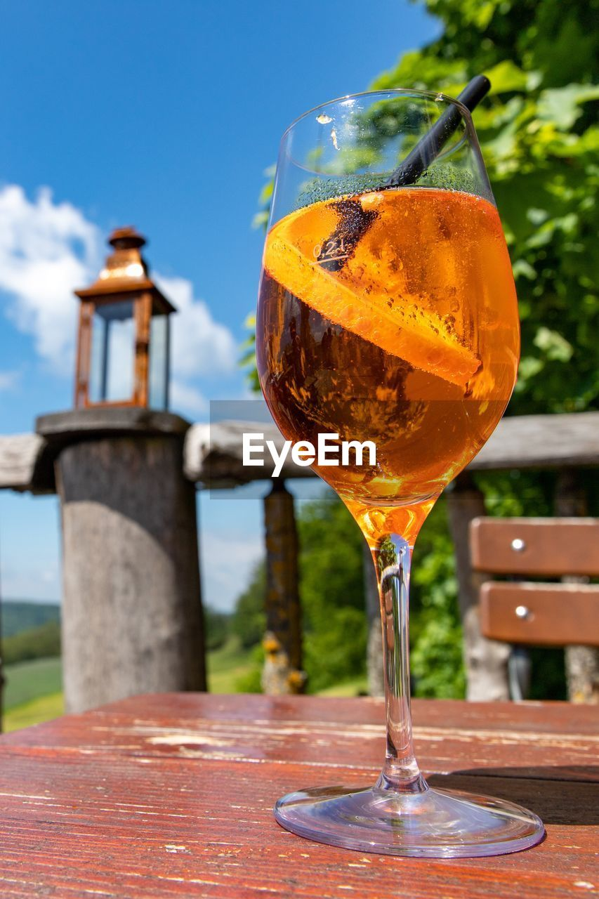 refreshment, drink, food and drink, glass, alcohol, table, focus on foreground, close-up, wineglass, no people, drinking glass, wine, freshness, sky, wood - material, still life, day, orange color, food, glass - material, outdoors, orange, aperitif, wooden post