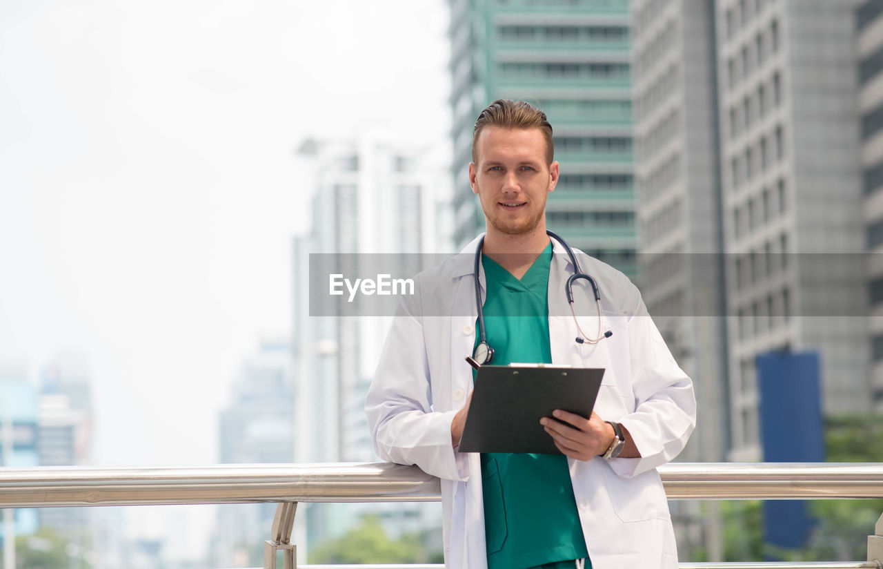 architecture, occupation, city, built structure, waist up, standing, building exterior, doctor, one person, building, clothing, front view, men, day, lab coat, adult, digital tablet, portrait, office building exterior, skyscraper