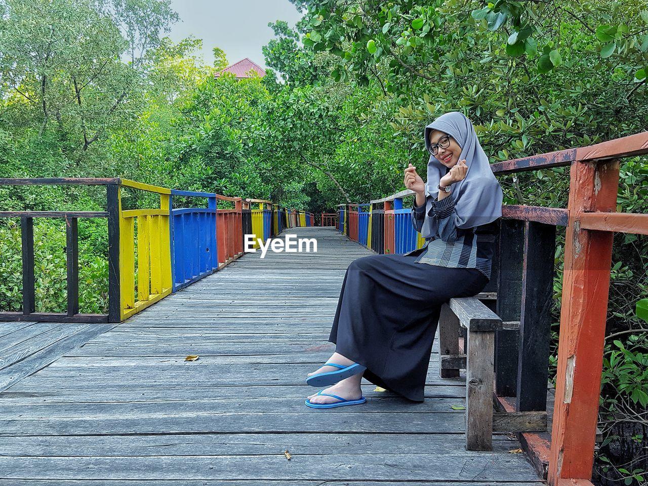 Portrait of smiling woman sitting on footbridge against trees